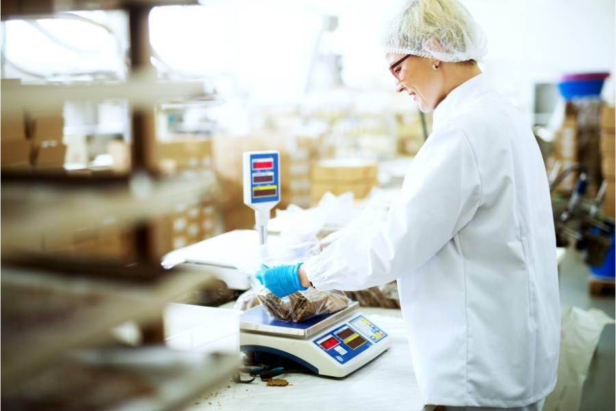 Ζύγισμα προϊόντος από εργάτη σε βιομηχανία τροφίμων